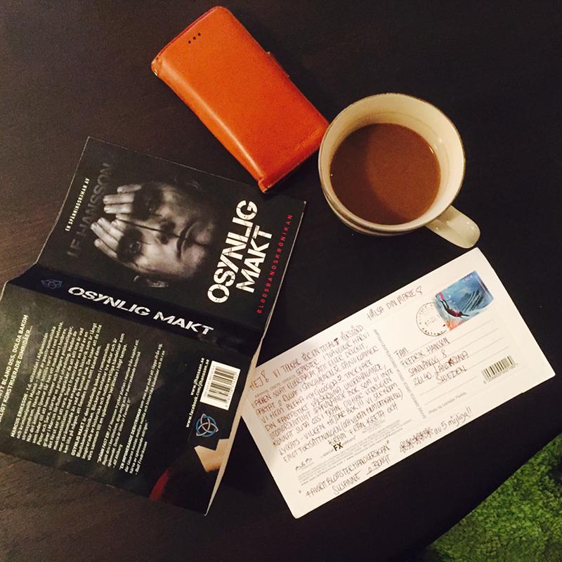 Boken ligger på ett bord med kaffekopp och telefon